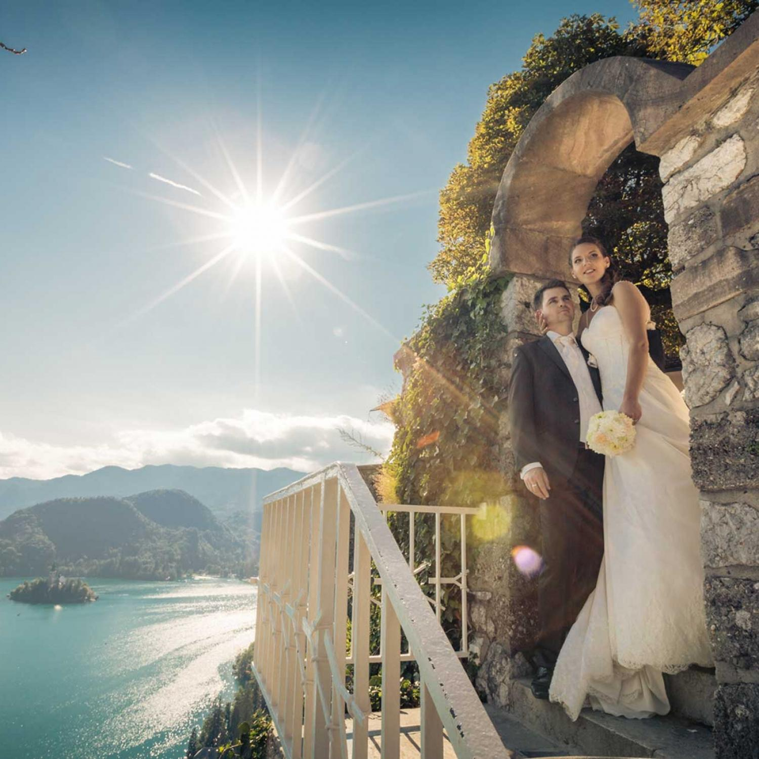Couple posing on the stairs with Bled Island in the distance
