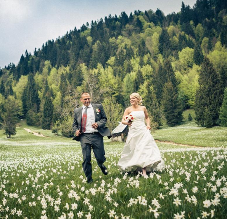 Newlywed couple running on a grass field