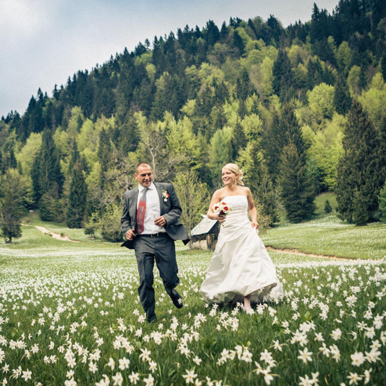 Newlywed couple running on a grass field