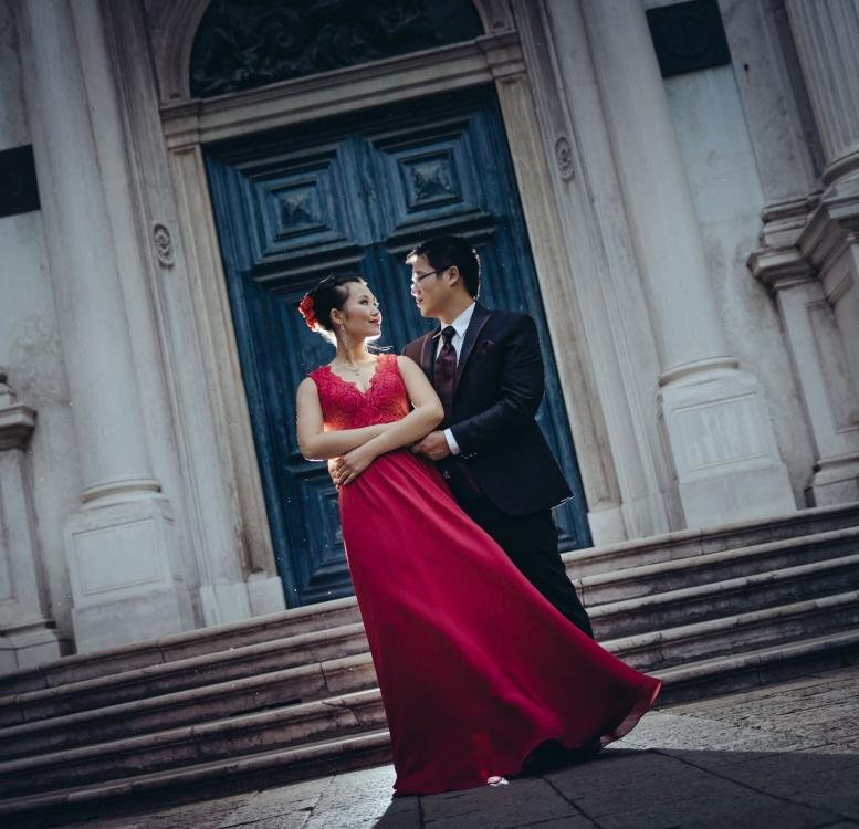 威尼斯 Couple posing in front of blue door in Venice