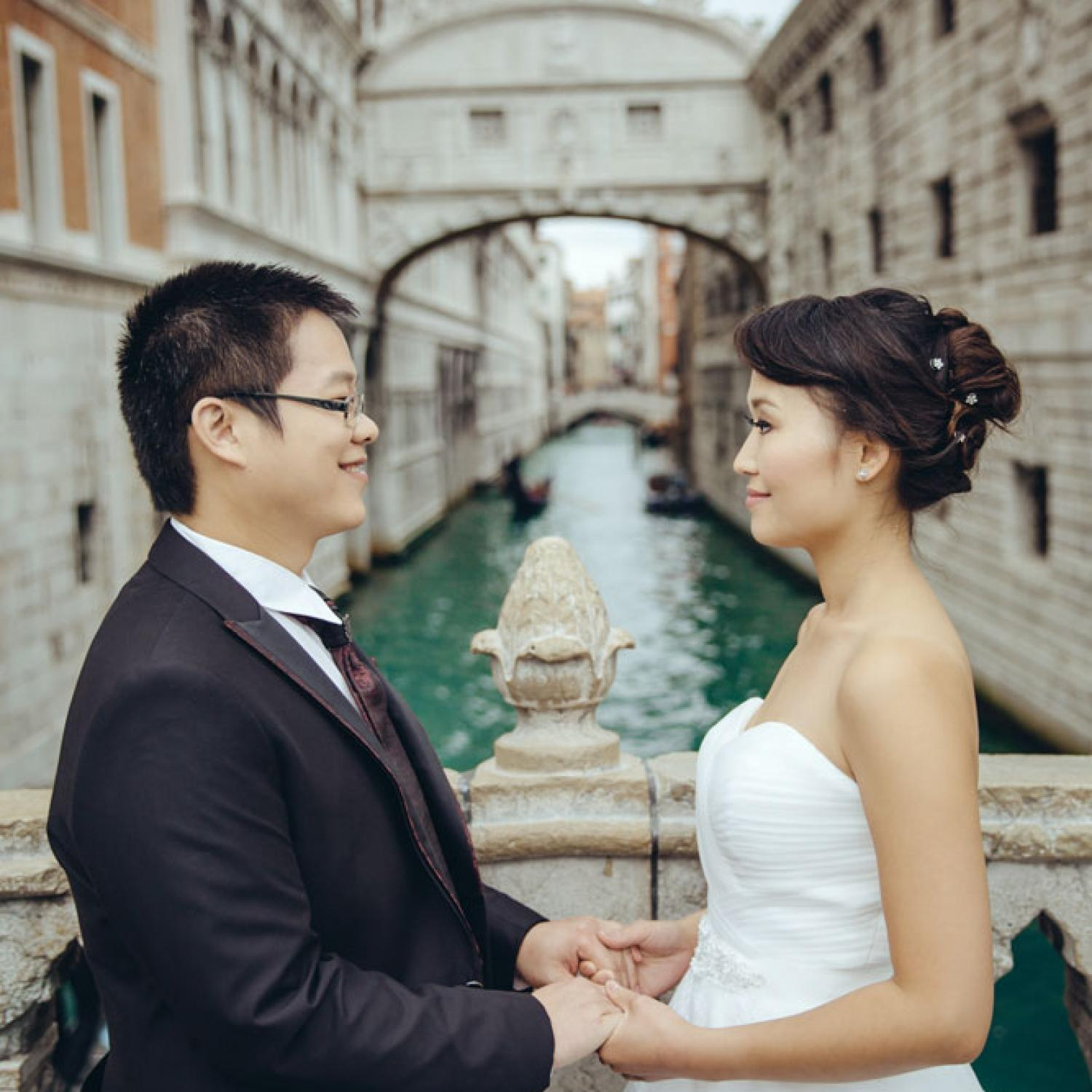 Couple posing for pre-wedding photo with a Bridge of Sighs in the back