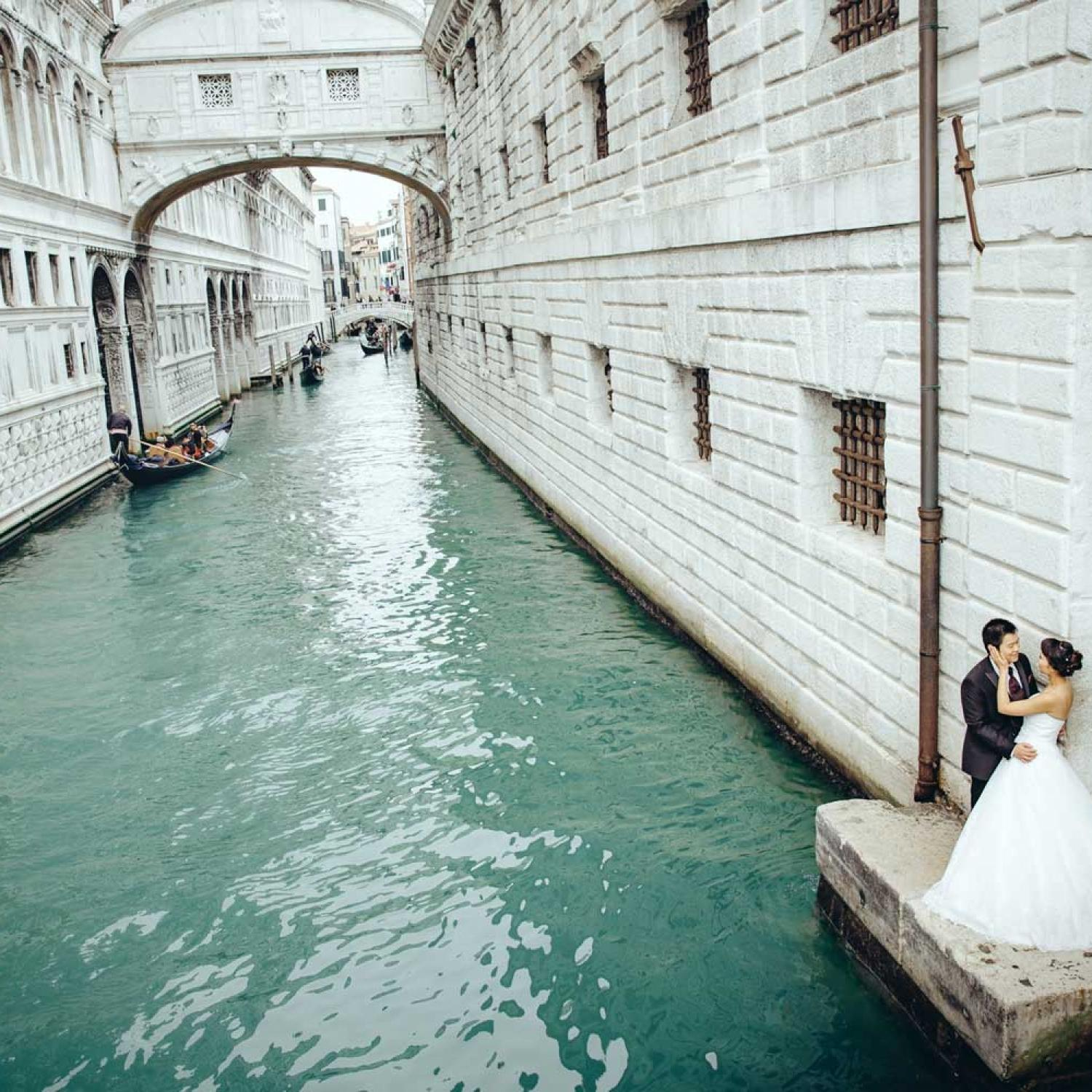 Couple posing next to the water canal in Venice