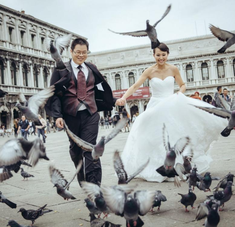 Couple running towards pigeons in Venice